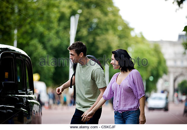 A young couple talking to a taxi driver - Stock Image