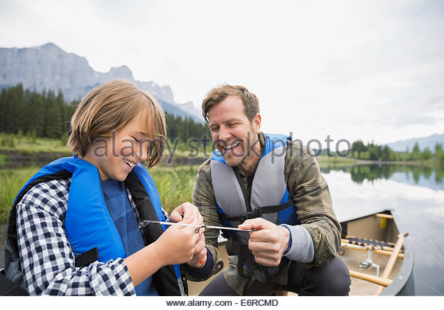 Father and son tying fishing lure to line - Stock Image