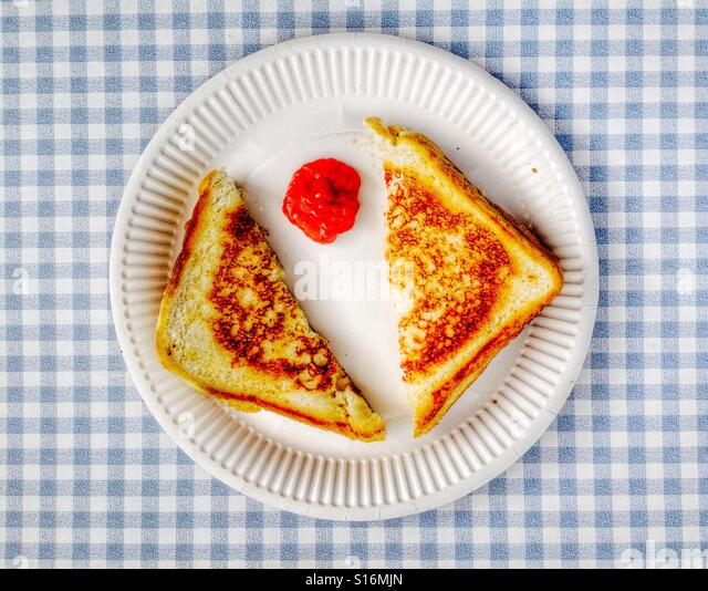 Fried cheese sandwich with tomato ketchup on paper plate - Stock-Bilder