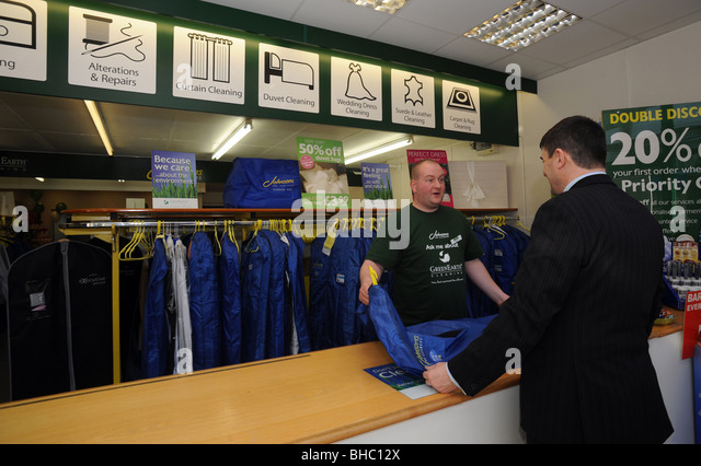 A man picks up his dry cleaning at a branch of johnsons the dry cleaners - Stock Image