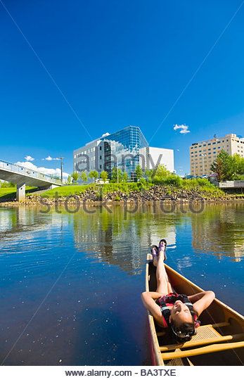 Young woman relaxes in a tandem canoe and floating downstream on the Chena river in Fairbanks during Summer - Stock Image