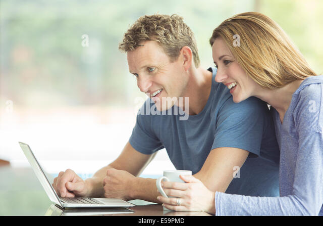 Couple using laptop together - Stock Image