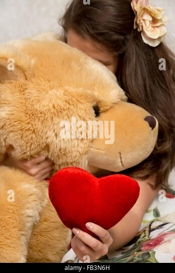 Girl holds stuffed giant bear and hides behind him - Stock Image