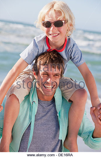 Father carrying son on shoulders at beach - Stock Image