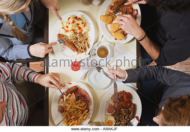 Four friends eating at cafe - Stock Image