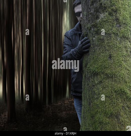 a dark man behind a tree - Stock Image