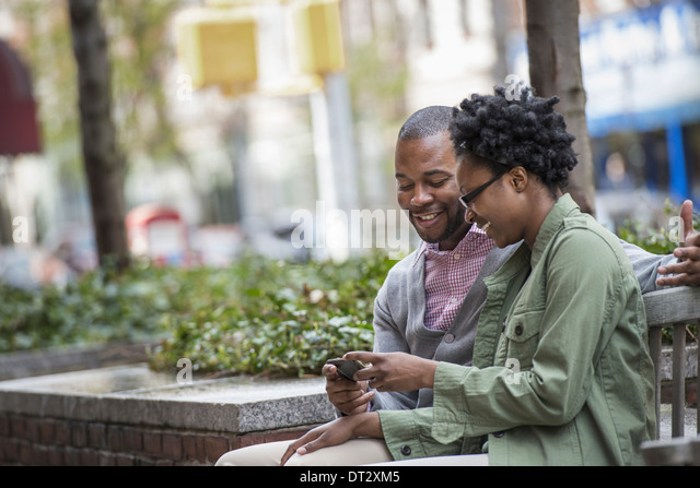 A couple sitting side by side and looking at a phone screen - Stock Image