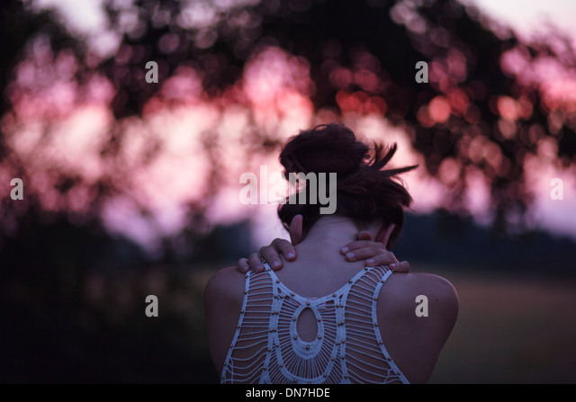 Rear view of a young woman with folded arms - Stock Image
