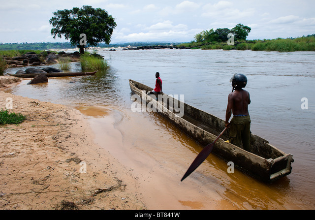 Two men float in a wooden boat on the river Congo - Stock-Bilder