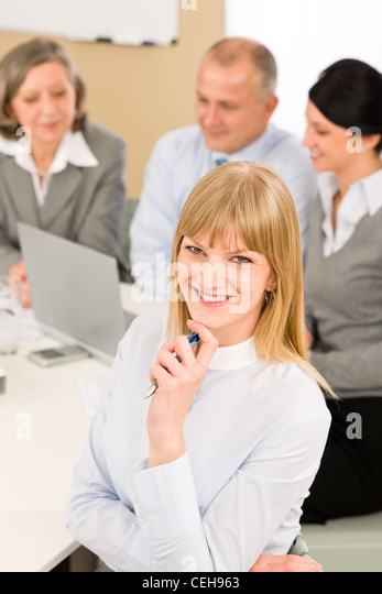 Young executive woman looking camera during meeting with team colleagues - Stock Image