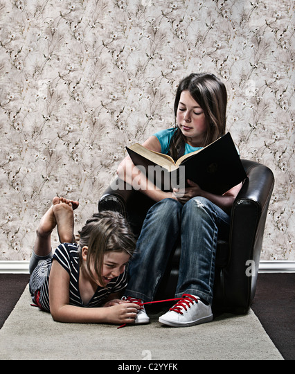 Girl Tying Shoelace of Sister Whilst She Reads a Book - Stock Image