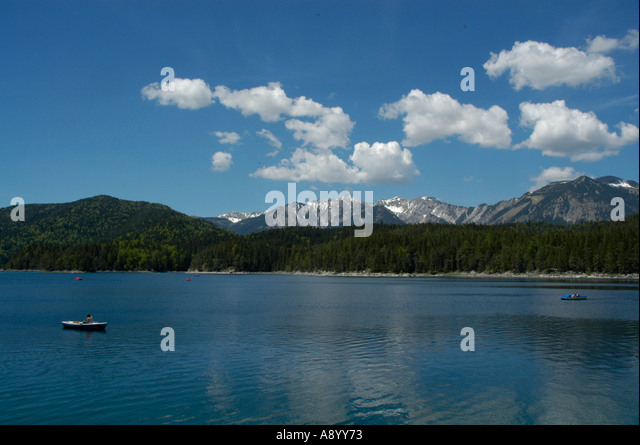 Blue sky with white clouds above a clear lake with a rowing boat Eibsee near Grainau Upper Bavaria Germany - Stock Image