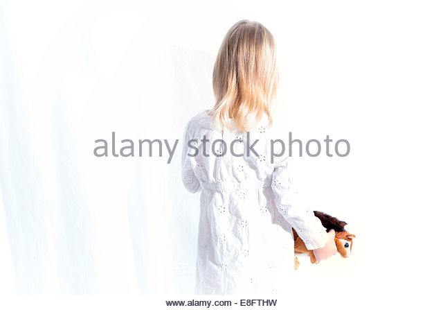 USA, Colorado, Girl holding toy squirrel, rear view - Stock Image