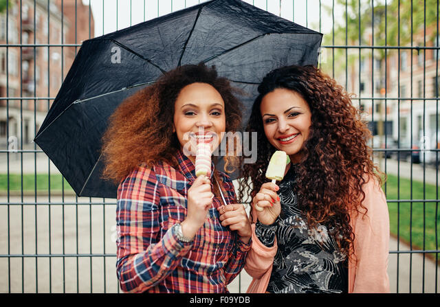 Portrait of two young women standing under umbrella eating an ice cream. Happy young female friends outdoor. - Stock-Bilder
