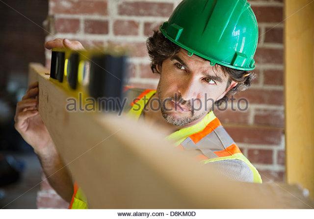 Tradesman leveling wooden plank at construction site - Stock-Bilder