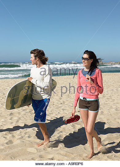 Young couple going surfing - Stock Image