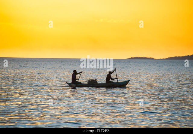 Backlight of fishermen in a little fishing boat at sunset, Lake Malawi, Cape Maclear, Malawi, Africa - Stock Image