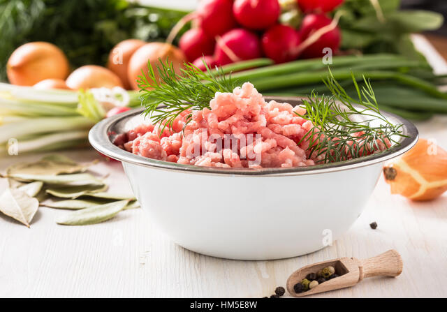 Raw ground meat in white bowl. Minced pork on a background of fresh organic vegetables - Stock Image