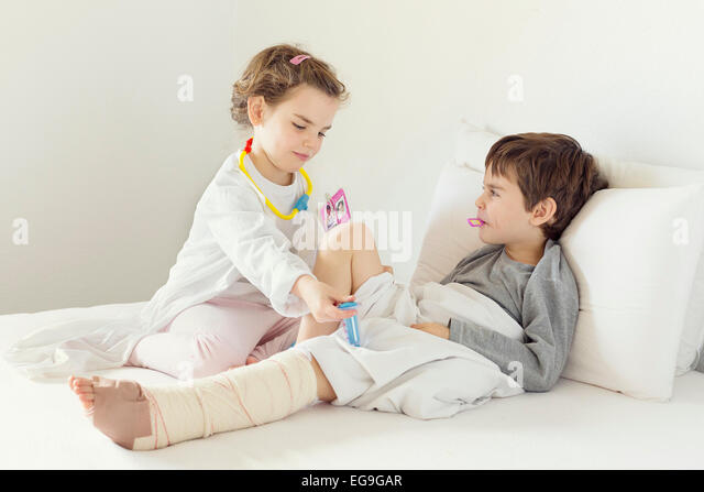 Girl playing nurse to her brother in bed - Stock Image