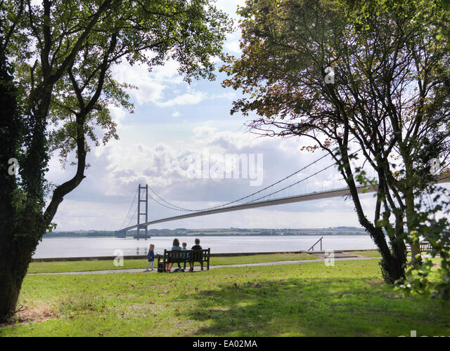 Family sitting together on bench looking at suspension bridge Humber Bridge UK was built in 1981 - Stock-Bilder
