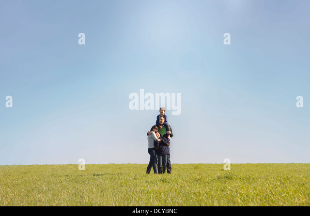 Family Hugging on Field - Stock Image