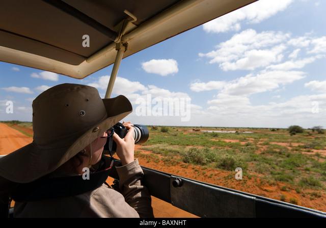 Woman photographying during safari tour, Tsavo East National Park, Coast, Kenya - Stock Image