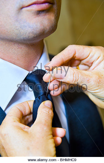 Groom putting a cravat pin on - Stock Image