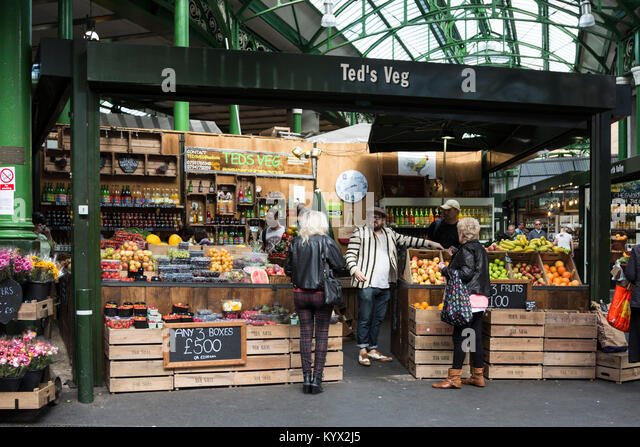 Grocer with customers at Borough Market, London, England, United Kingdom - Stock Image