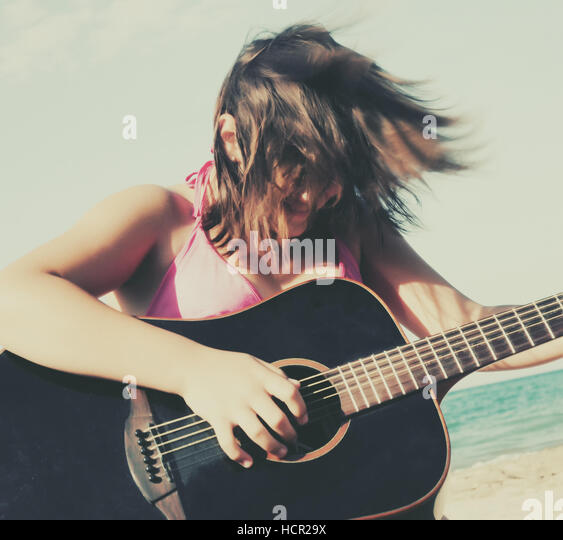 Girl playing guitar on the beach - Stock Image