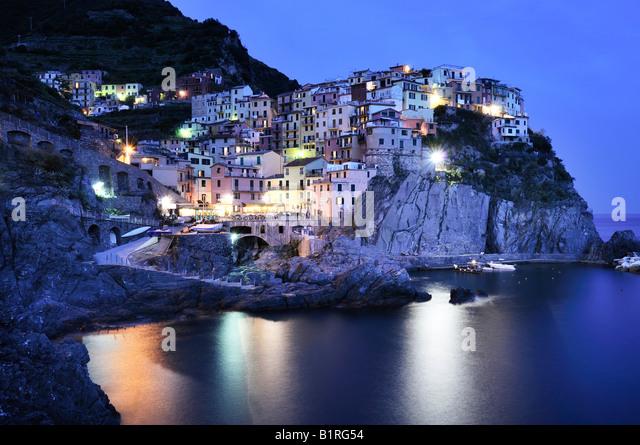 Village of Manarola nestled atop steep coastline at dusk, Liguria, Cinque Terre, Italy, Europe - Stock Image
