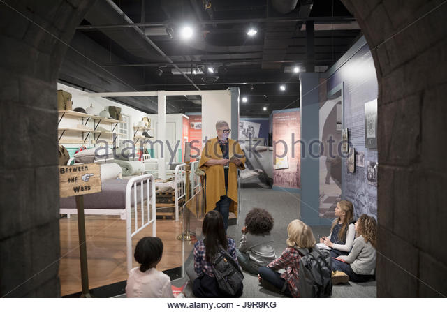 Docent explaining exhibits to students on field trip in war museum - Stock-Bilder