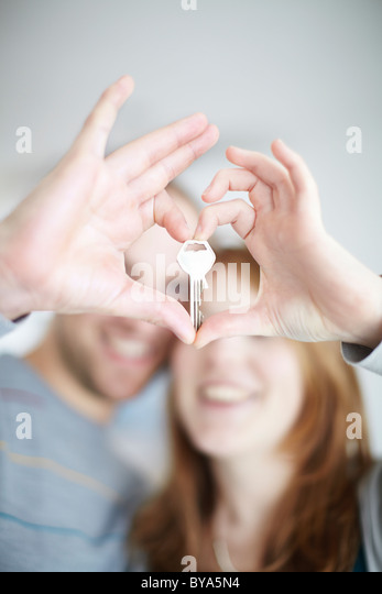 A happy couple holding a key - Stock Image