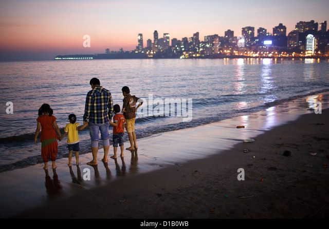 A father with children (family) on Girgaum Chowpatty (Girgaum beach) after the sunset in Mumbai, India. - Stock Image