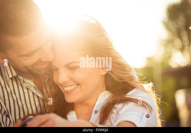 Happy couple having great time together - photographed at sunset against sun - Stock-Bilder