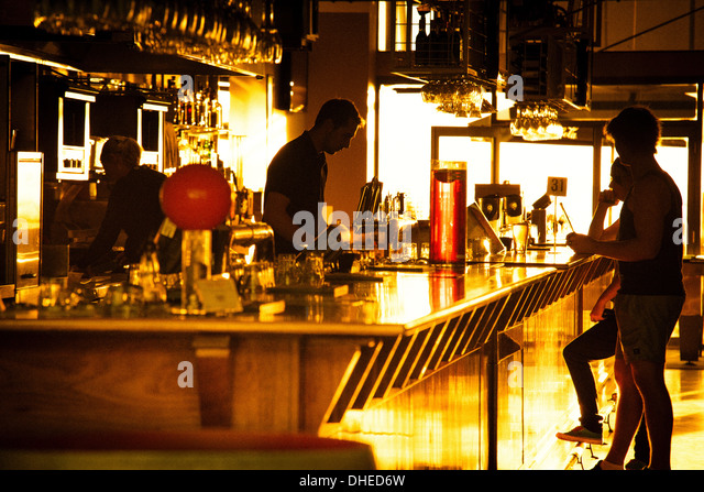 Staff and patrons of a Glenelg bar (in Adelaide) silhouetted against the sunset. - Stock Image