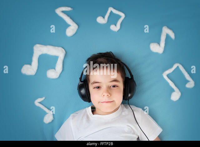 little boy on blue blanket background with headphones - Stock-Bilder