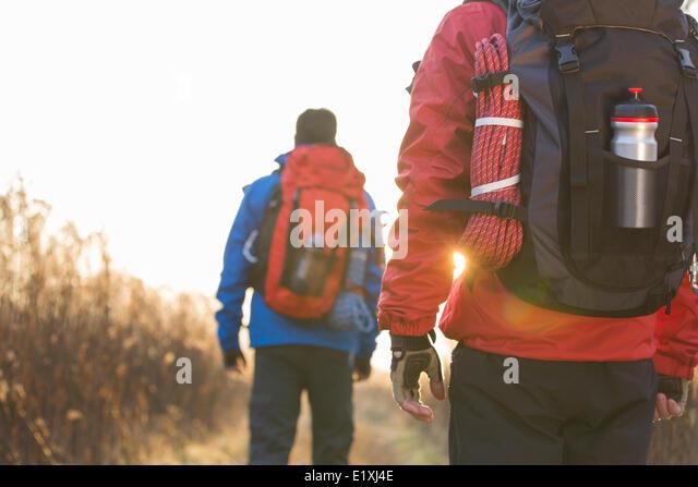Rear view of male backpackers walking in field - Stock Image