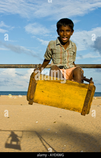 Indian Boy on a Swing on the Beach in Mamallapuram South India - Stock-Bilder
