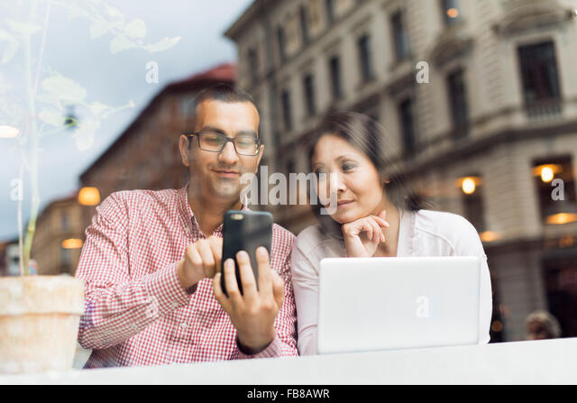 Sweden, Uppland, Stockholm, Man and woman using smart phone in cafe - Stock-Bilder