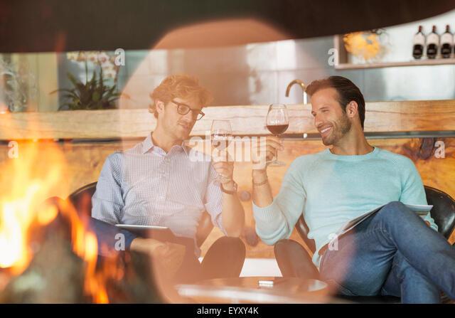 Men wine tasting at fireplace in winery tasting room - Stock-Bilder