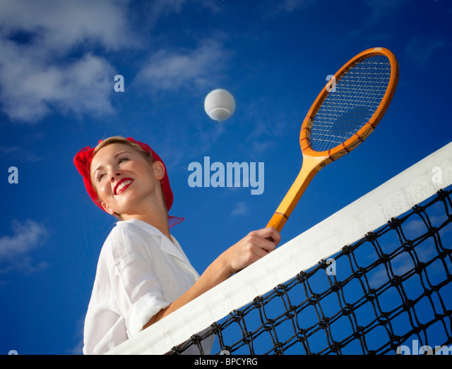 Low angle view of young woman playing tennis - Stock Image