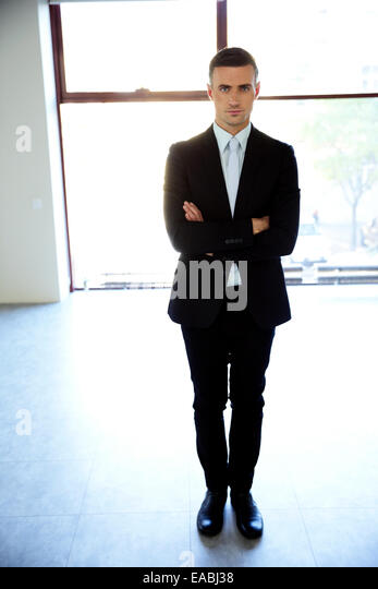 Full length portrait of a businessman standing with arms folded at office - Stock Image