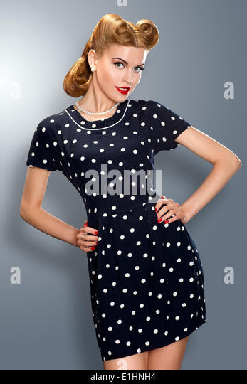 Pin-up girl in retro vintage old-fashioned dress in romantic pose - Stock Image