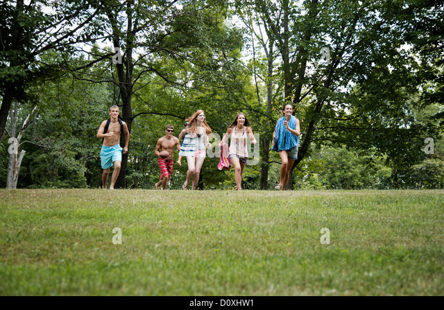 Five friends running on grass, front view - Stock Image
