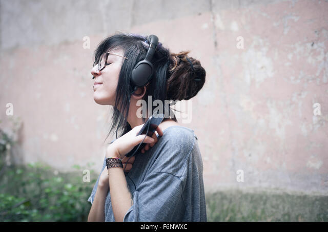 Teen woman with headphones listening music with deep emotion - Stock Image