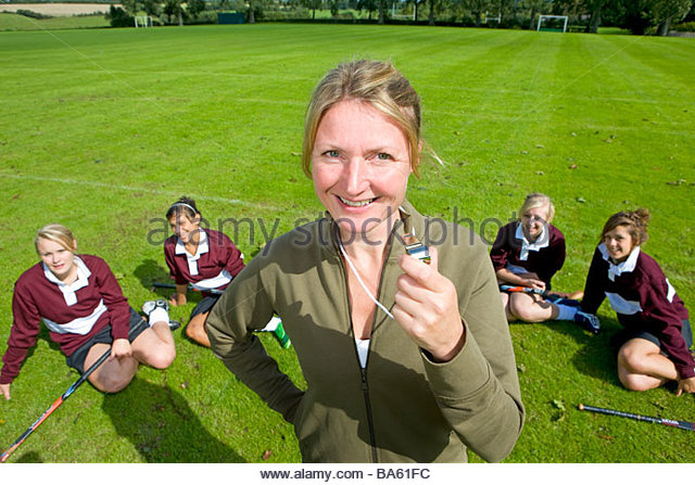 Portrait of smiling field hockey coach holding whistle - Stock Image