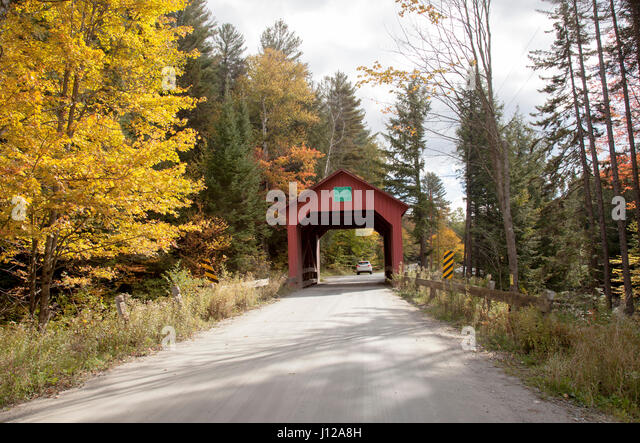 Red covered wooden bridge with an American flag in Vermont, countryside - Stock Image