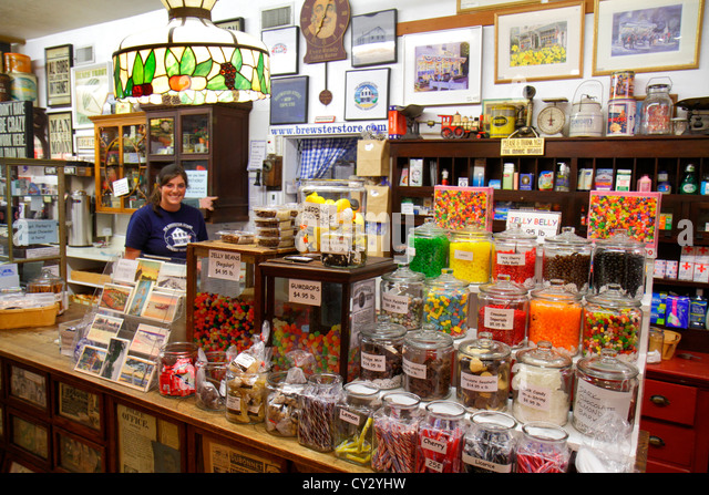 Massachusetts Cape Cod Brewster The Brewster Store groceries general merchandise inside interior candy woman clerk - Stock Image