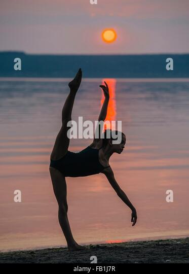 Girl by ocean at sunset on one leg, bending forward arm and leg raised - Stock Image