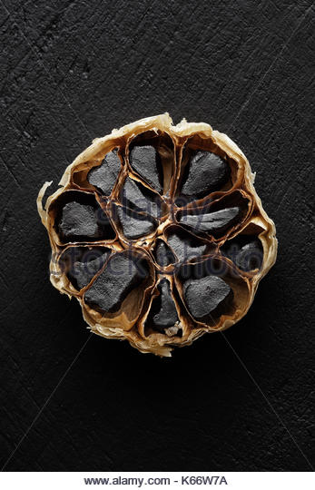 Black Garlic cross-section photographed from above on dark background - Stock Image